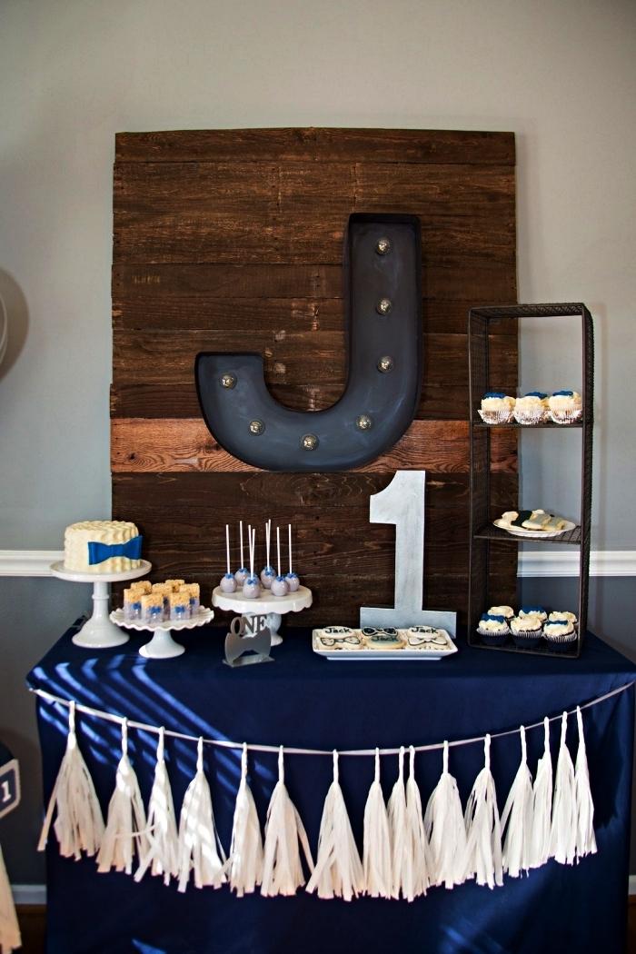 idée pour réaliser une decoration anniversaire 1 an garçon, buffet d'anniversaire 1 an décoré d'une guirlande à tassels avec un tableau en bois et métal comme toile de fond