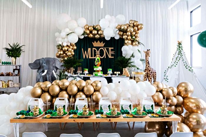 idée déco anniversaire 1 an sur le thème safari, déco de table anniversaire safari en vert et or, arche de ballons en blanc et or