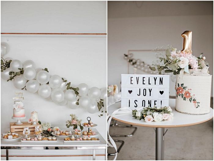 buffet d'anniversaire 1 an en style champêtre décoré d'une arche de ballons et de feuilles d'eucalyptus, gâteau d'anniversaire 1 an pour fille décoré de fleurs et de cake topper ballon chiffre