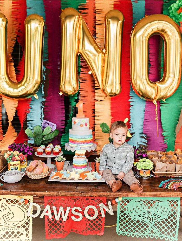 une fête d'anniversaire 1 an mexicaine, buffet gourmand sur le thème fiesta mexicaine avec toile de fond en guirlande à franges
