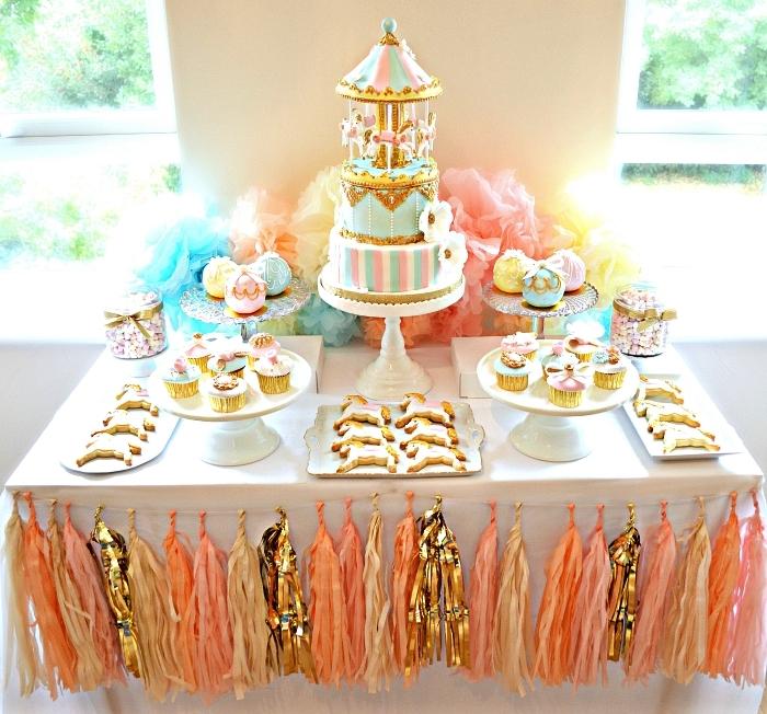 jolie déco de table sur le theme anniversaire carrousel, candy bar d'anniversaire décoré d'une guirlande tassels en rose, or et pêche