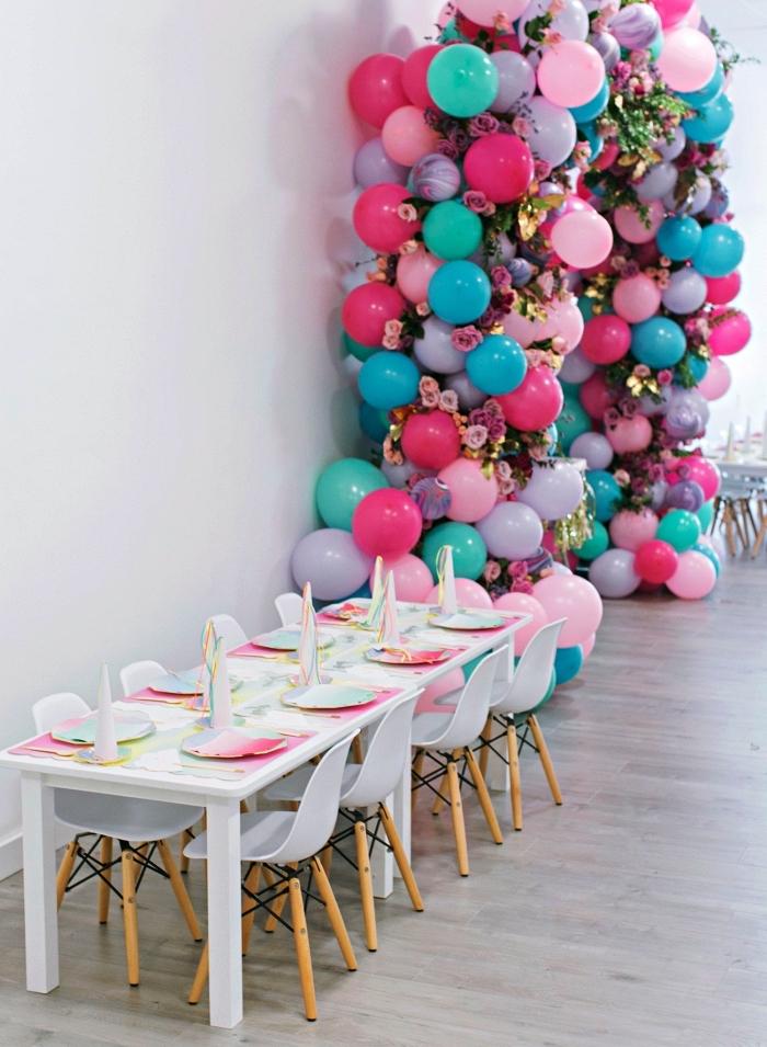 deco table anniversaire sur le thème licorne avec un set de table iridescent, arche de ballons rose, bleu et violet