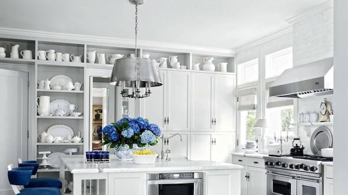 bouquet de fleurs bleues et chaises bleues dans une cuisine blanche et grise traditionnelle avec beaucoup de vaisselle blanche exposée