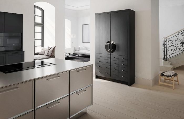 design intérieur moderne dans une cuisine aux murs blancs avec îlot en taupe et meubles rangement en noir mat