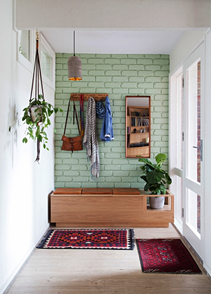 aménagement entrée de style bohème chic, banquette d'entrée en bois vintage installée contre un mur d'accent en briques peint en vert amande