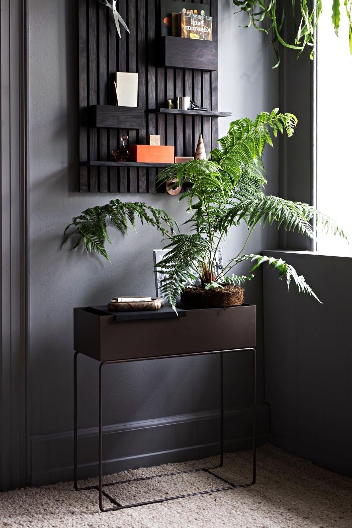 déco d'entrée élégante avec petite console en métal noir mat et un organisateur mural en bois peint en noir