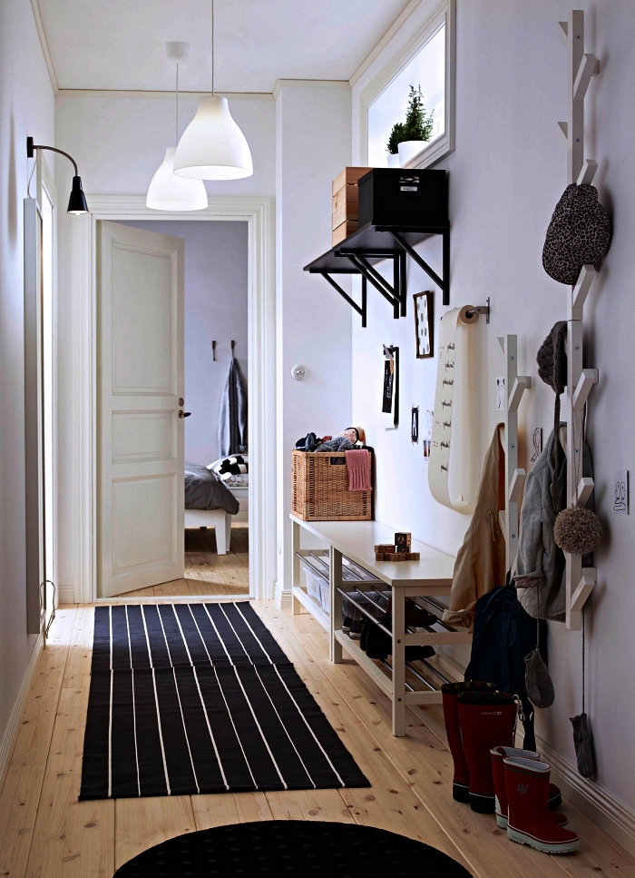 banc d entrée avec rangement pour chaussures et une penderie murale en bois peinte blanche, petite entrée de style scandinave au sol en parquet bois et aux murs peints blancs