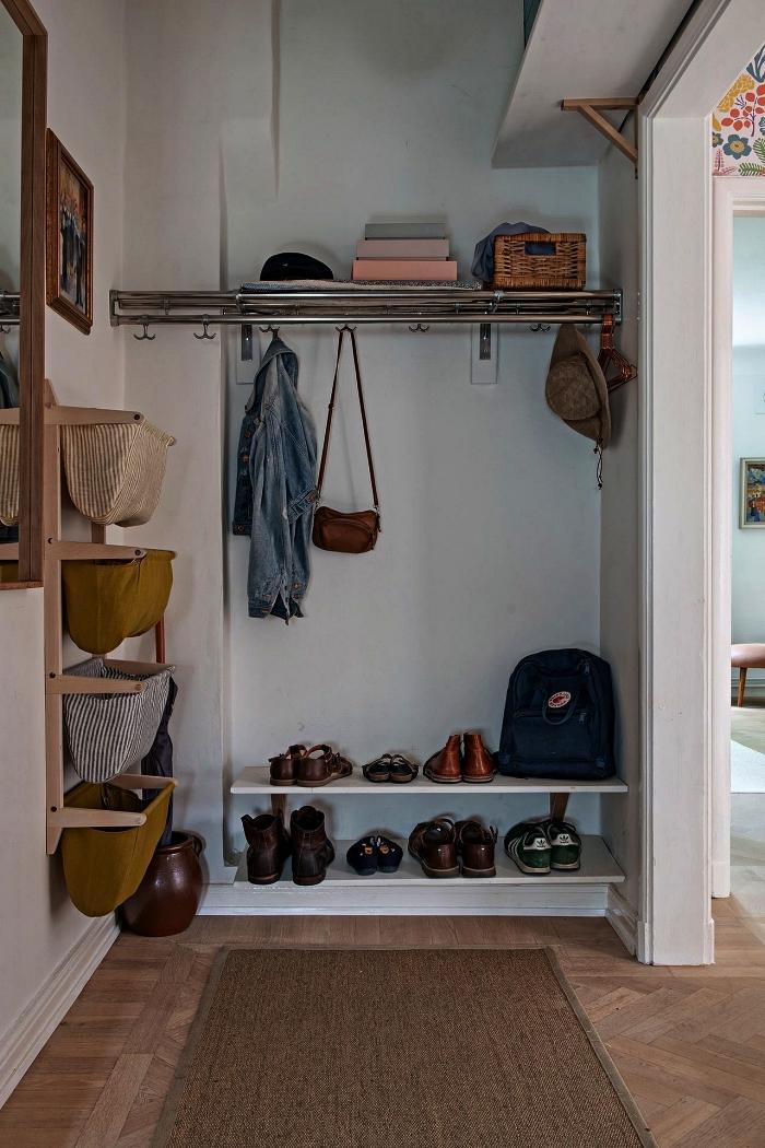 coin de rangement optimisé dans une petite entrée avec étagères à chaussures et un porte-manteau télescopique