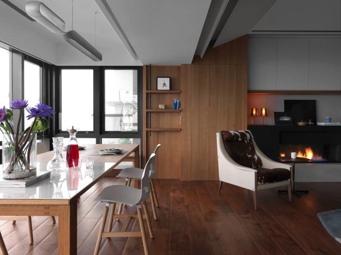 décoration salon ouvert de style contemporain avec cheminée noire et meubles bois, exemple de décoration murale bois