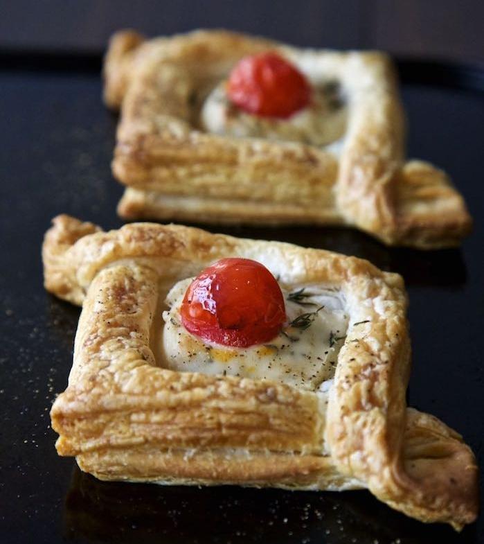 exemple d apero carré de feuiilleté avec fromage et tomate cerise dans une sorte de bateau et herbes
