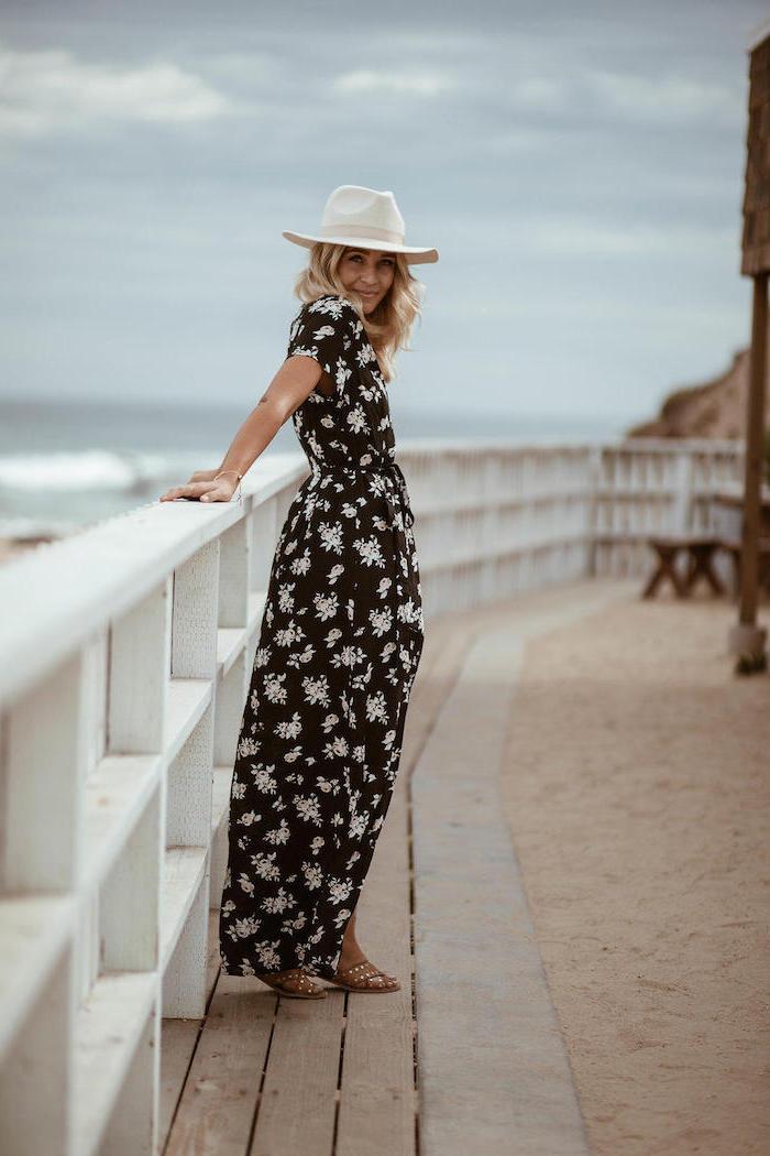 Été en automne tenue femme, longue robe noire à fleurs blanches, femme au bord de la mer, comment s'habiller, mode automne hiver 2019