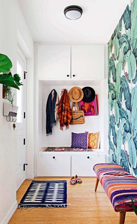 pan de mur en papier peint tropical dans un petit hall d'entrée blanc aux accents déco bohème chic, vestiaire d'entrée avec banc de rangement