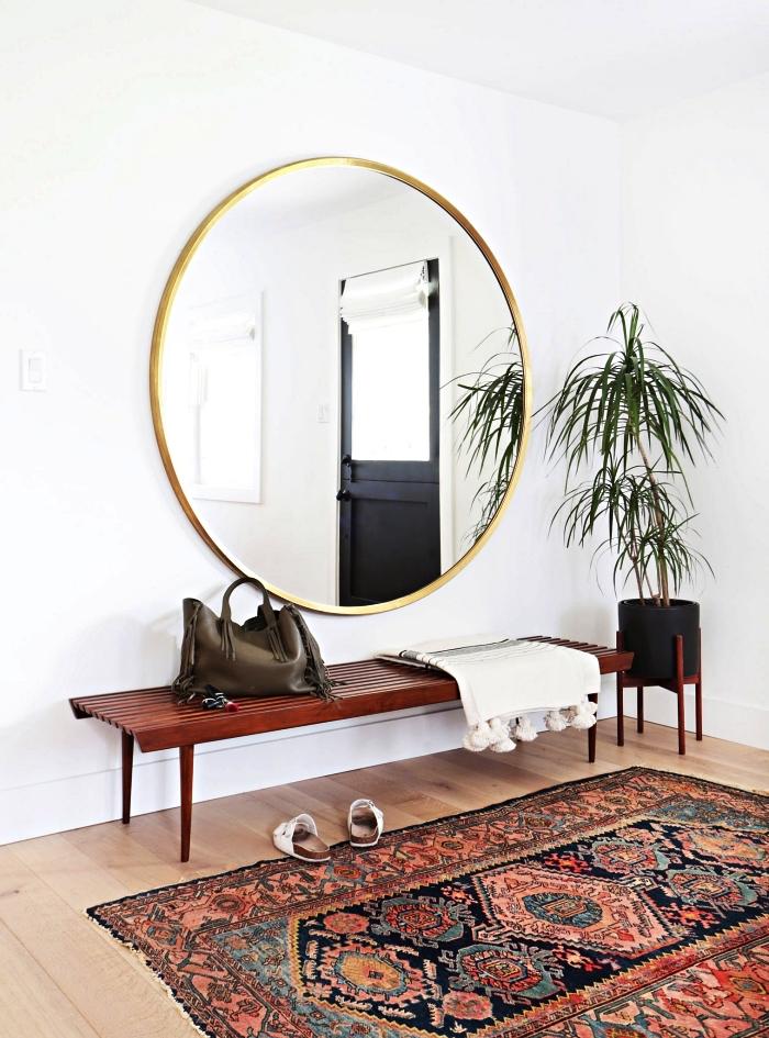 déco d'entrée avec banquette entrée vintage en dessous d'un miroir rond grande taille et un tapis persan