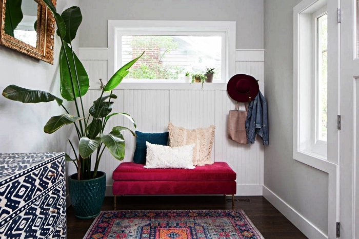 aménagement entrée accueillante avec banc matelassé en velours, un miroir à cadre vintage et une grande plante verte