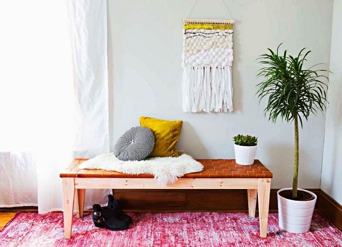 petit hall d'entrée de style bohème chic avec banc en bois et cuir, une tapisserie murale et un tapis rose fuchsia effet délavé