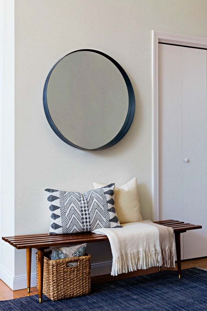 banquette entrée décoratif avec coussins ethnique chic et panier de rangement en rotin surmontée d'un grand miroir rond