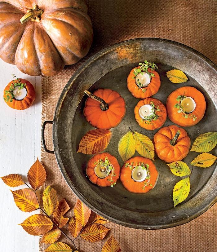 deco d automne a faire soi meme, potirons creusés avec bougie à l intérieur flottants dans de l eau avec des feuilles mortes