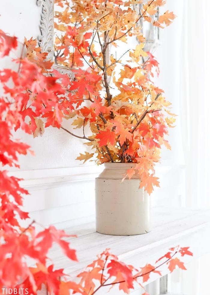 idée de branches avec des feuilles d automne dans un vase blanc sur le bord d une cheminée blanche, idée d activité automne