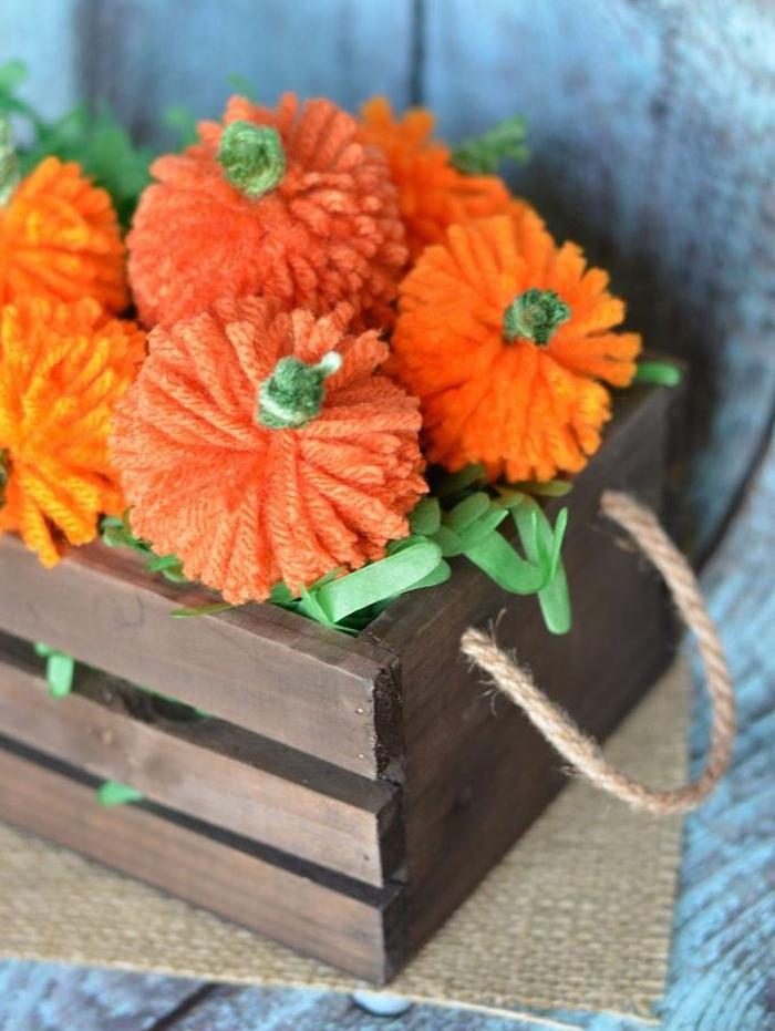 petites citrouilles en laine orange avec des tiges vertes dans une cagette de bois, deco automne a faire soi meme