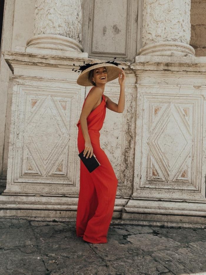 comment s habiller pour un mariage, modèle de combinaison rouge assortit avec pochette noire et capeline beige