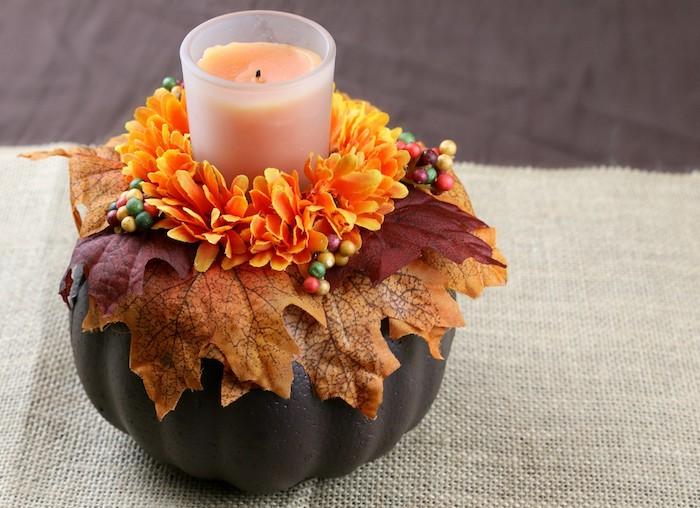 idee deco table automne avec une citrouille repeinte de peinture marron avec deco de feuilles d automne et fleurs orange et bougie au centre