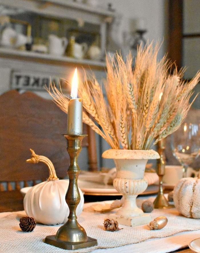 bougeoir en or et des épis de blé pour décorer un chemin de table en jute avec des pommes de pin et citrouilles habillées de tissu