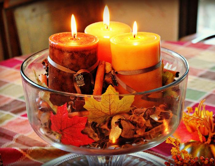 idee de contenant de verre rempli de feuilles d automne morte ramassées, batons de cannelle et des bougies aromatiques a l interieur