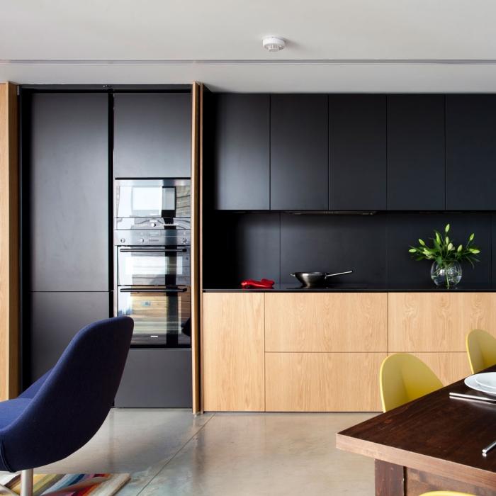 comment aménager une cuisine moderne en longueur, exemple de cuisine noire et bois au plancher effet ciment