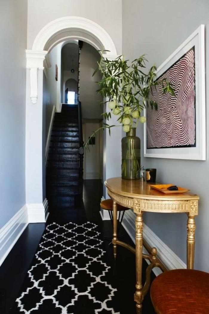 Noir sol et murs gris, meuble étroit couloir, décoration simple et efficace, vase avec fleurs sur table semi ronde