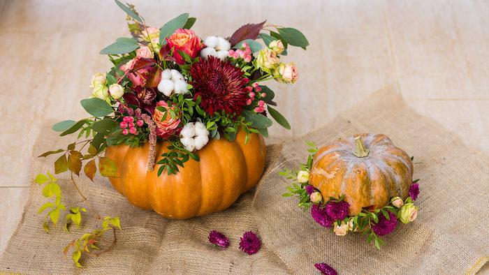 centre de table fleurie, idee deco table automne avec bouquet de fleurs dans une citrouille halloween creusée