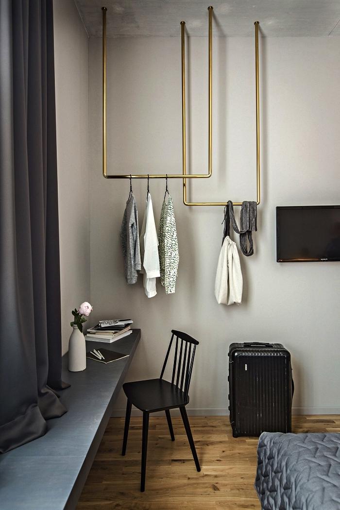 aménagement d'une chambre avec coin dressing, penderie suspendue au plafond en laiton pour exposer ses plus beaux vêtements