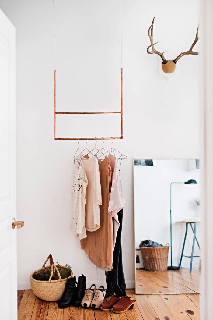 coin dressing avec penderie minimaliste en cuivre suspendue au plafond et un grand miroir rectangulaire posé contre le mur