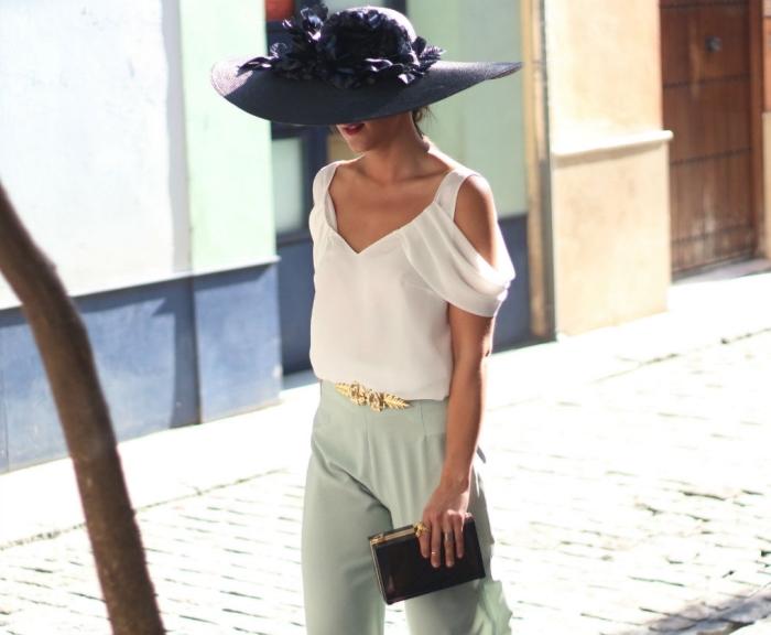 idée de tenue de cérémonie femme élégante, modèle de pantalon vert pastel avec blouse blanche et capeline noire