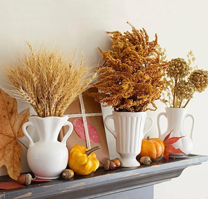épis de blé et autres végétaux d automne dans des vases blancs de porcelaine sur le rebord d une cheminée avec deco glands, potirons et feuilles mortes