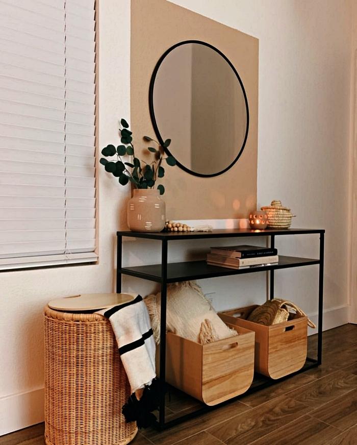 deco entree en bois et noir avec console métallique légère, un miroir rond tendance et des paniers de rangements en bois et osier