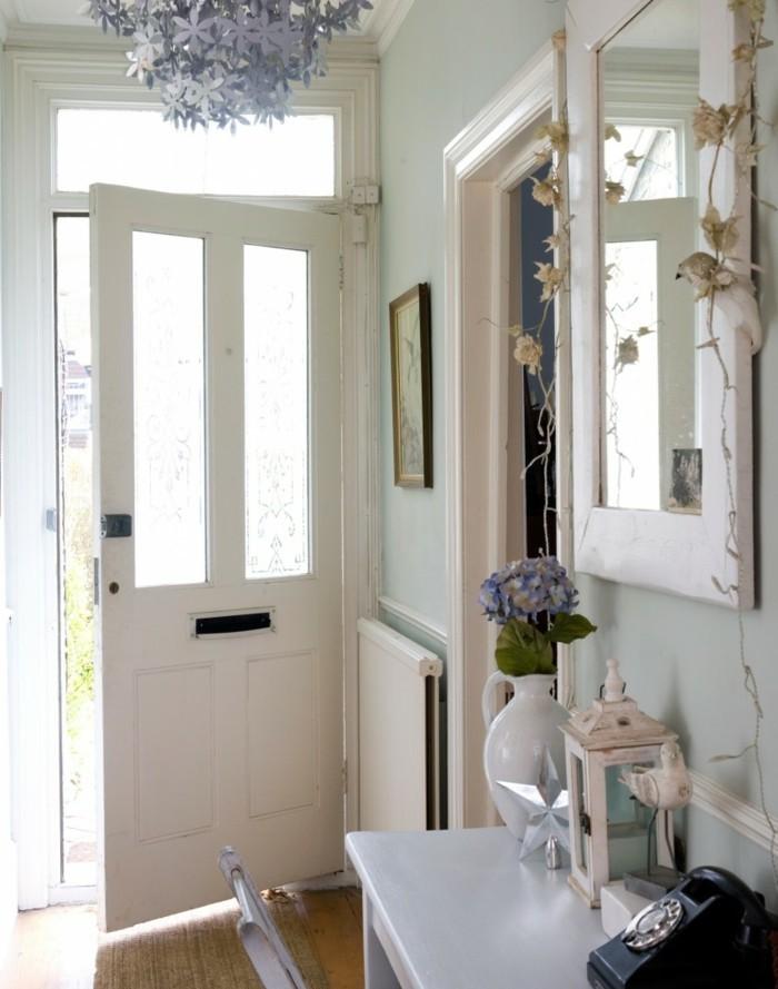 Porte d'entrée blanche, lustre décoratif, deco couloir long et étroit papier peint et peinture tendance, miroir blanc, vase avec fleurs