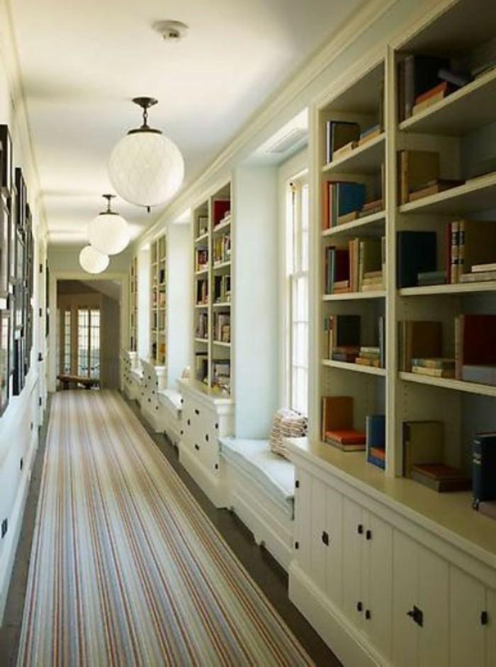 Étagères ouvertes avec beaucoup de livres, tapis long, vestiaire étroit de couloir, belle décoration entrée chic