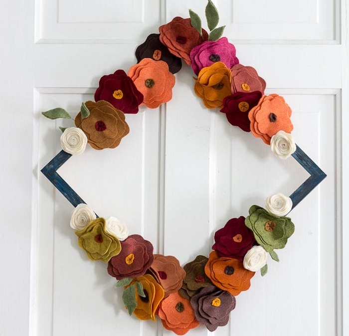 faire une couronne d automne de fleurs de feutrine aux couleurs automnales collées sur un cadre de bois pour creer une deco de porte