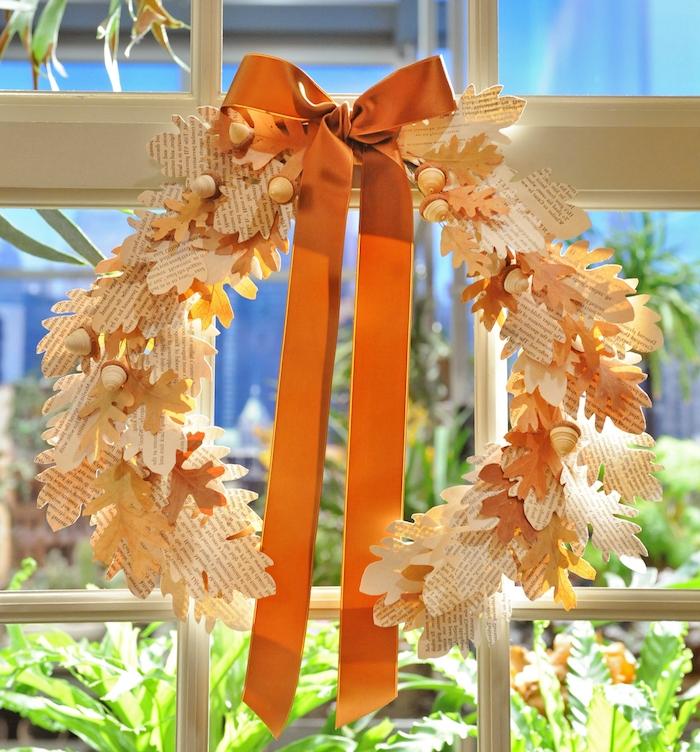 exemple original de couronne automne de feuilles d automne en papier journal avec deco de ruban orange pour decorer une fenetre