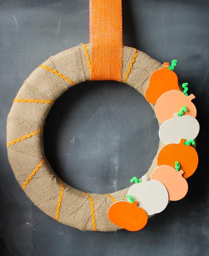 modele de couronne automne en cercle de mousse décoré de bande de jute avec deco de figurines de citrouilles en bois avec suspension sur bande de jute orange