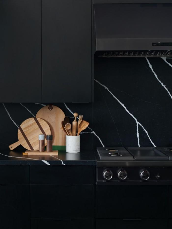 design contemporain dans une cuisine look total noir avec meubles haut cuisine en noir mat et crédence marbre noir
