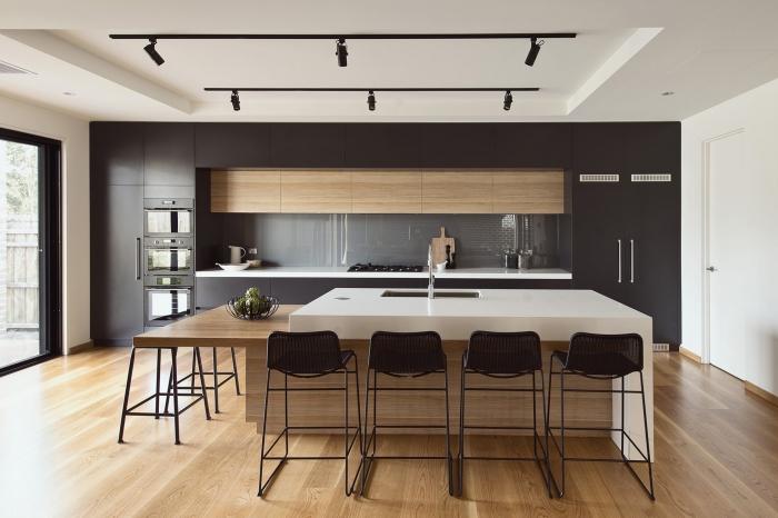aménagement cuisine linéaire avec îlot table à manger, décoration cuisine bois et noir avec crédence gris et accents blancs
