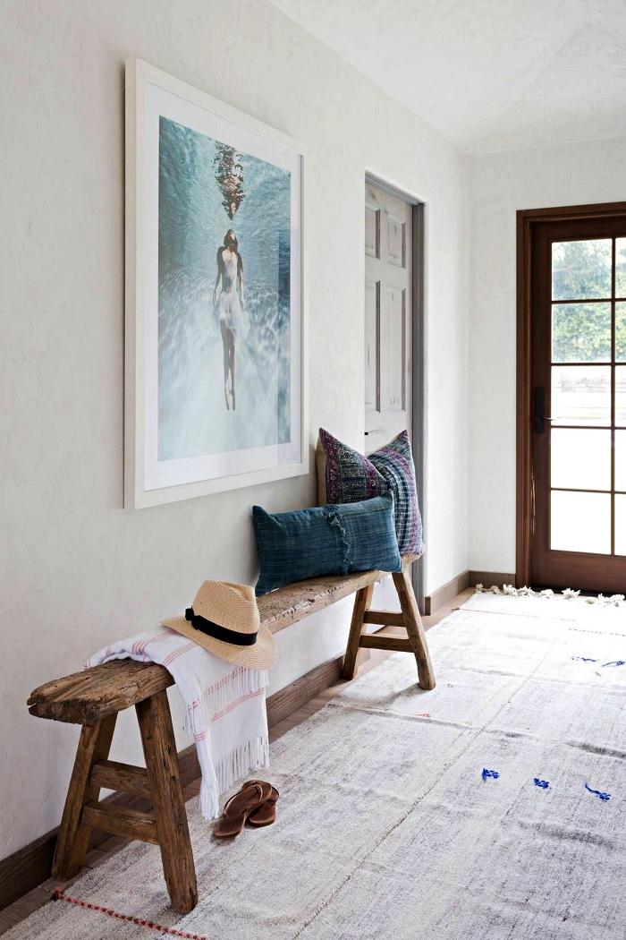 déco entrée maison de style bohème chic avec banc d'entrée en bois rustique et un grand cadre photo à motif plage