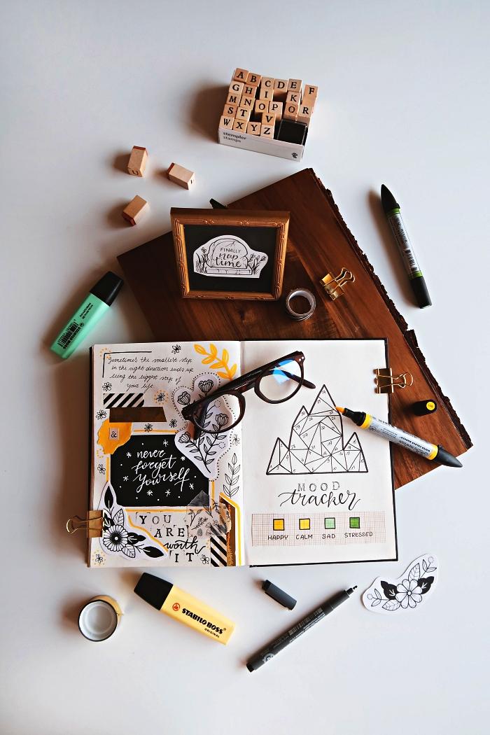 idée bullet journal créatif décoré d'illustrations florales et de coupures, suivi d'humeurs au design géométrique avec code par couleurs