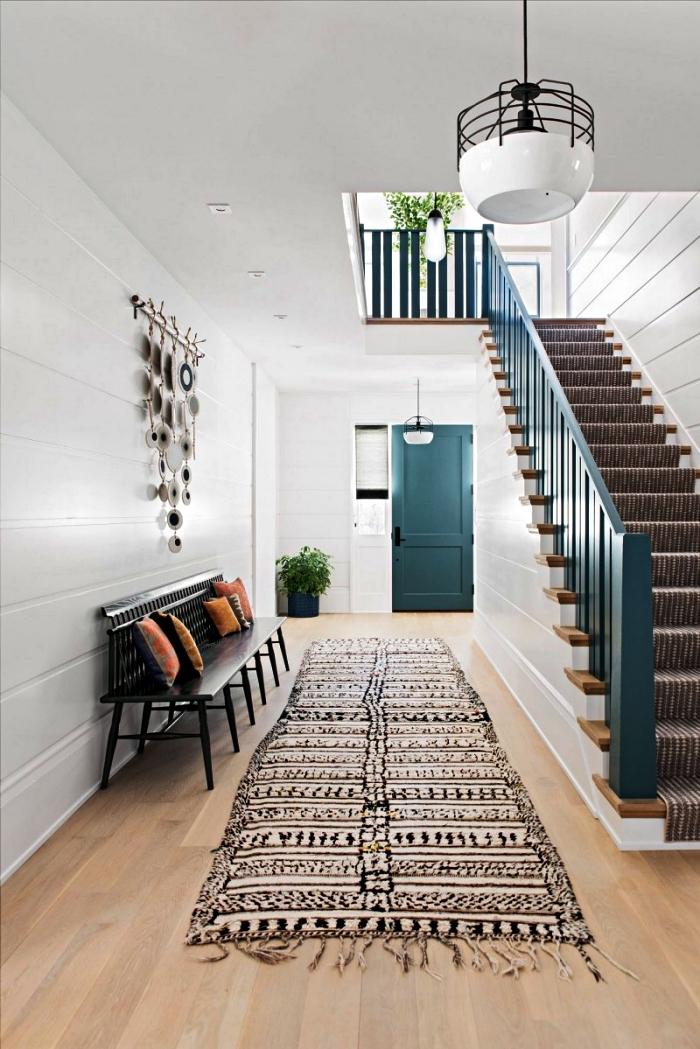 déco entrée maison de style ethnique chic avec banc noir, tapis ethnique et décoration murale originale