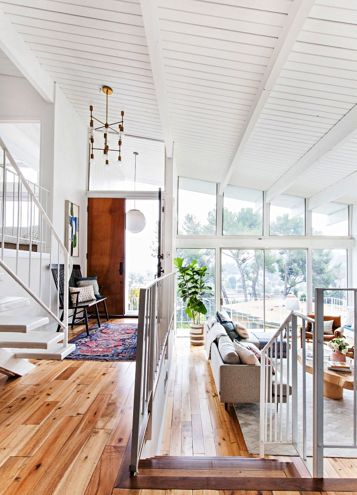 déco entrée maison contemporaine aux larges baies vitrées, décoration d'entrée avec tapis persan et banc décoratif
