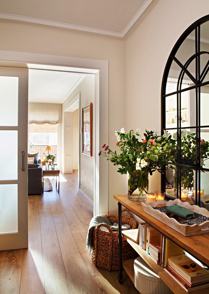 déco entrée maison de style campagne chic avec console en bois, miroir fenêtre à cadre noir et un panier de rangement en osier