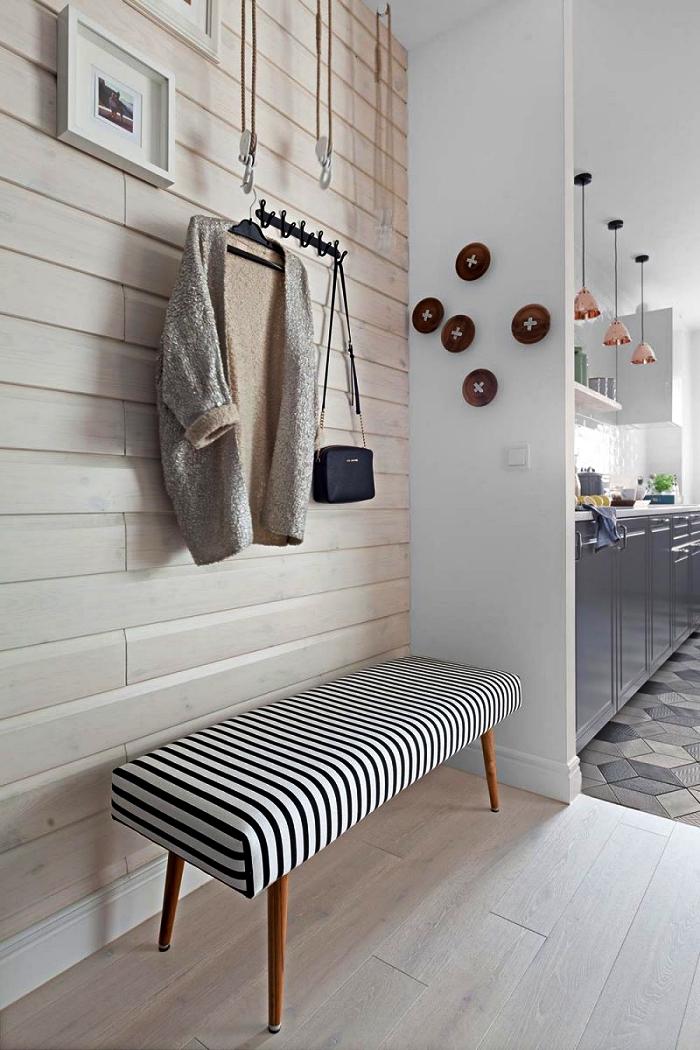 coin d'entrée avec banc rayé noir et blanc posé contré un mur d'accent en panneau bois clair