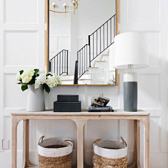 coin déco dans le hall d'entrée avec une console en bois, des paniers de rangement en osier et un miroir rectangulaire à cadre laiton