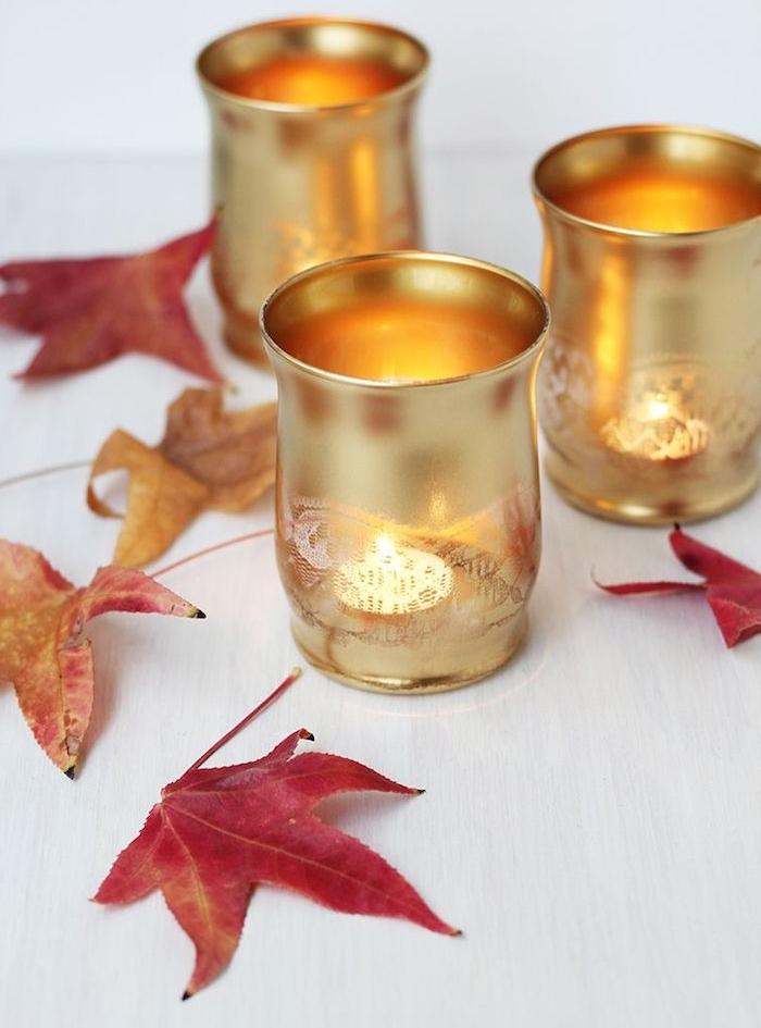 bougeoirs de verre repeints de peinture couleur or à effet dentelle sur une table décorée de feuilles mortes, deco table automne simple